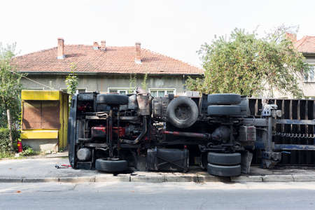 overturned: An accident with an overturned truck in the main street of a small city.