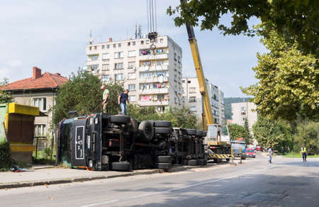 troyan: Troyan, Bulgaria - September 22, 2015: Crashed truck with its cargo at the pavement near the road. Editorial