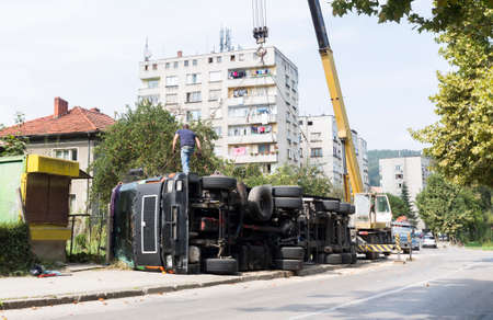 overturned: A view of the rear wheels of a overturned truck on a small street in an accident.