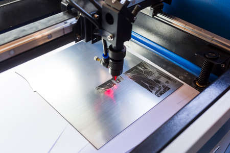 cutting tools: Laser machine is cutting an image on a flat sheet ot steel in a university laboratory. Stock Photo