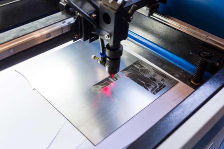 Laser machine is cutting an image on a flat sheet ot steel in a university laboratory. Standard-Bild