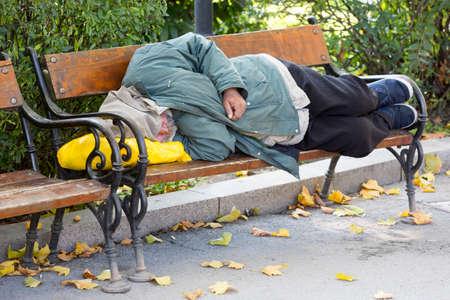 Persona sin hogar está durmiendo en un banco en un frío día de otoño en un parque en el país más pobre de la Unión Europea Bulgaria. Foto de archivo