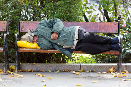marginalized: Sofia, Bulgaria - October 28, 2015: Homeless person is sleeping on a bench in a cold autumn day in a park in European unions poorest country Bulgaria. Editorial