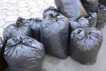 black plastic garbage bag: Black garbage bags on the street near trash recycle bins. Stock Photo