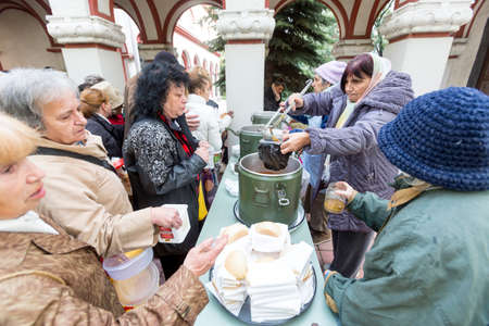 despaired: Sofia, Bulgaria - October 26, 2015: Church personnel is giving food to the christian believers who have come to the morning prayer.