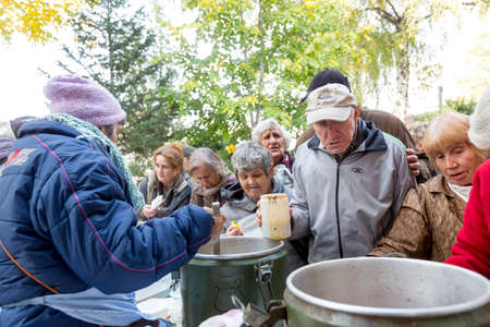 food distribution: Sofia, Bulgaria - October 26, 2015: Church personnel is giving food to the christian believers who have come to the morning prayer.