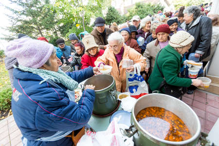 religious: Sofia, Bulgaria - October 26, 2015: Church personnel is giving food to the christian believers who have come to the morning prayer.