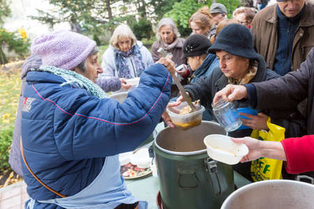 give charity: Sofia, Bulgaria - October 26, 2015: Church personnel is giving food to the christian believers who have come to the morning prayer.
