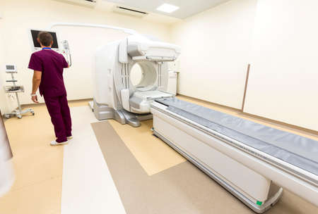 computed: A CT scan, also called X-ray computed tomography (X-ray CT) or computerized axial tomography scan (CAT scan) in a new modern cancer treatment hospital. Doctor adjusting the machine.
