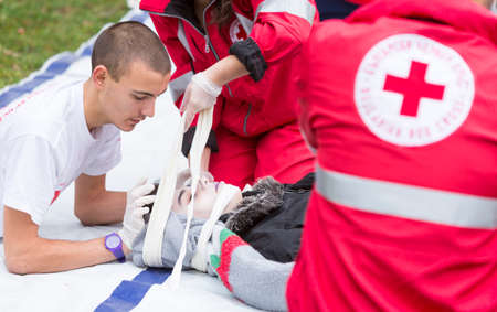 Sofia, Bulgaria - December 5, 2015: Volunteers from the Bulgarian Red Cross Youth Organization are participating in a training of saving people from a building during an earthquake. 免版税图像 - 53571939