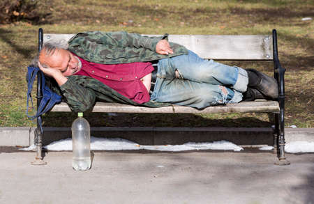 raggedy: Sofia, Bulgaria - January 8, 2016: A homeless man is sleeping on a bench in a park in Bulgarias capital Sofia. Years after joining the EU the country is still struggling with great poverty among its citizens.