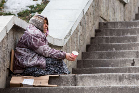social outcast: Sofia, Bulgaria - January 8, 2016: A homeless gypsy woman is begging for money in the center of Bulgarias capital Sofia. Years after joining the EU the country is still struggling with poverty among its citizens