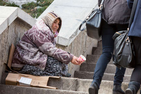 homelessness: Sofia, Bulgaria - January 8, 2016: A homeless gypsy woman is begging for money in the center of Bulgarias capital Sofia. Years after joining the EU the country is still struggling with poverty among its citizens