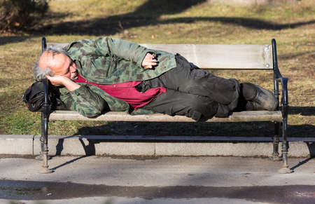 waif: Sofia, Bulgaria - January 14, 2016: Homeless man is sleeping on a bench in Sofia. Bulgaria is EUs poorest country.