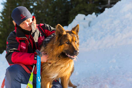 rescuer: Sofia, Bulgaria - January 28, 2016: Rescuer from the Mountain Rescue Service at Bulgarian Red Cross and his dog are participating in a training for saving people in an avalanche.