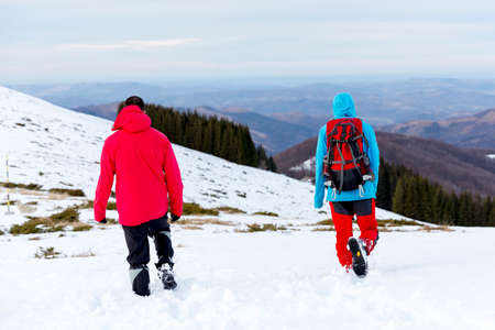two men: Two men are walking high in the snow in the mountain during the winter.