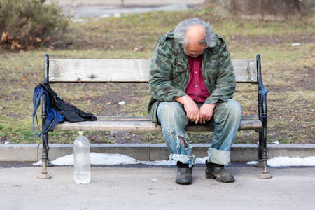 A homeless man is sitting and sleeping on a bench in a park in Bulgarias capital Sofia. Years after joining the EU the country is still struggling with great poverty among its citizens. Editorial