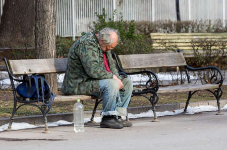 raggedy: A homeless man is sitting and sleeping on a bench in a park in Bulgarias capital Sofia. Years after joining the EU the country is still struggling with great poverty among its citizens. Editorial