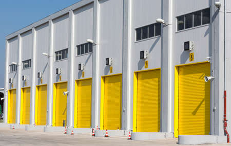 large doors: An industrial warehouse with eight large yellow drive-in doors for big trucks.
