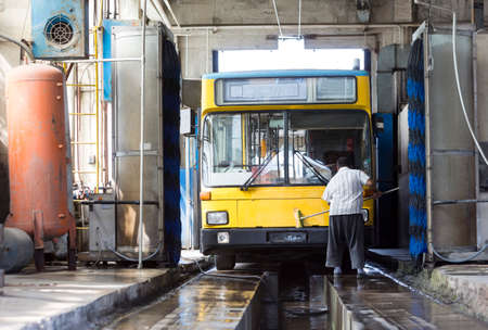 depot: The driver of the trolley car is washing the vehicle in the tram depot.