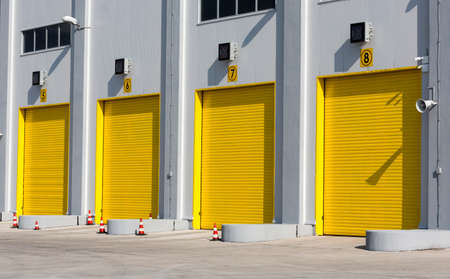 garage doors: Four yellow garage doors for high industial cargo trucks.