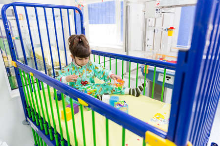 carotid: Sofia, Bulgaria - March 1, 2016: An young girl with a cardiac disease is playing in a bed in a cardilogical childrens hospital. High-quality treatment with modern equipment. Editorial