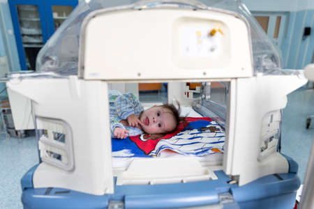 carotid: Sofia, Bulgaria - March 1, 2016: A baby with a cardiac disease is smiling in an incubator in a cardilogical childrens hospital. High-quality treatment with modern equipment.