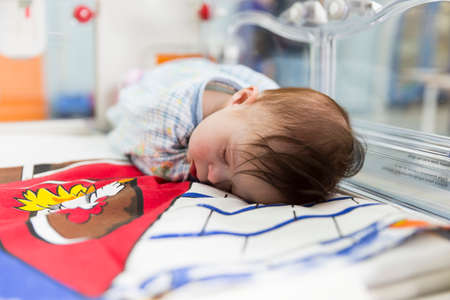 carotid: Sofia, Bulgaria - March 1, 2016: A baby with a cardiac disease is sleeping in an incubator in a cardilogical childrens hospital. High-quality treatment with modern equipment.