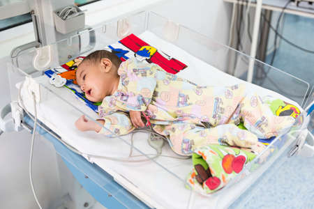 carotid: Sofia, Bulgaria - March 1, 2016: A baby with a cardiac disease is lying in a bed in a cardilogical childrens hospital. High-quality treatment with modern equipment.