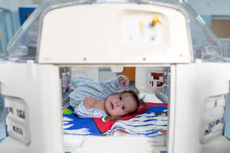reaching out: Sofia, Bulgaria - March 1, 2016: A baby with a cardiac disease is reaching out of an incubator in a cardilogical childrens hospital. High-quality treatment with modern equipment.