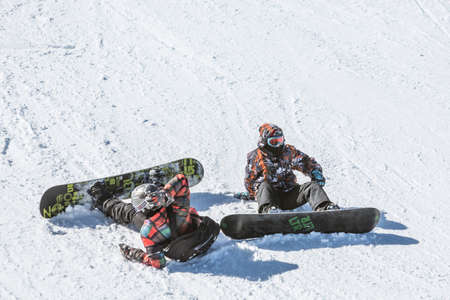 freestyle: Sofia, Bulgaria - March 12, 2016: Two teenage snowboarders are sitting on the ski slope just before a freestyle competition for skiers and snowboarders begins.
