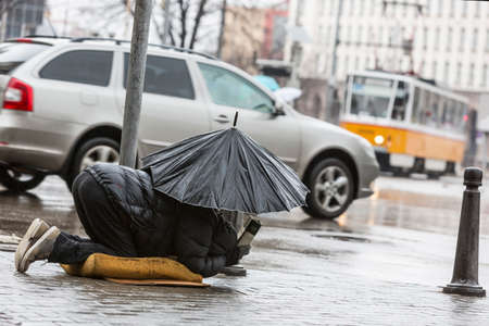 ugliness: Homeless beggar is begging holding umbrella in the rain at a main street in Sofia. Bulgaria is one of the poorest countries in Europe.