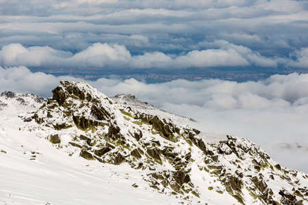 rocky peak: A rocky peak of Vitosha mountain covered with snow. View against the cloudy sky above Bulgarias capital Sofia.