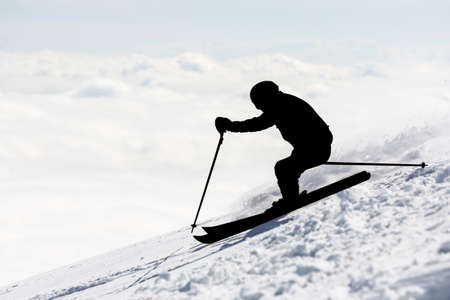 freestyle: The silhouette of a freestyle skier skiing at the top of a snowy peak of Vitosha mountain covered in clouds. He is participating in an freestyle competition of skiers and snowboarders during the weekend.