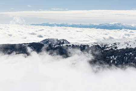 rocky peak: A rocky peak of Vitosha mountain covered with snow and fog. View against the cloudy sky.