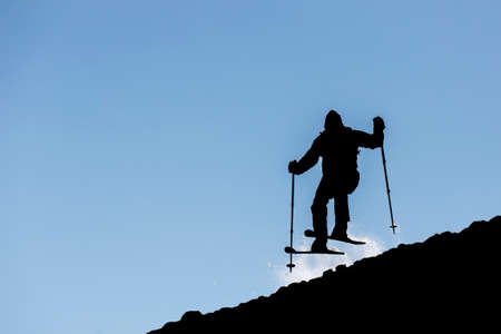 skier jumping: The silhouette of a freestyle skier jumping from the top of a peak of Vitosha mountain. He is participating in an freestyle competition of skiers and snowboarders during the weekend. Stock Photo