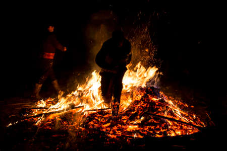 chased: Young man is jumping above the traditional fire during celebration of Sirni Zagovezni. It is believed that evil spirits are chased away with this fire rituals.