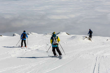 freestyle: Three skiers are at the top of a peak of Vitosha mountain. They are participating in an freestyle competition of skiers and snowboarders during the weekend.