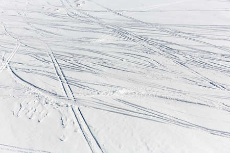 ski traces: Traces of skiers are seen from above on a ski slope in a snowy mounatin peak. Stock Photo