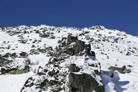 rocky peak: A rocky peak of Vitosha mountain covered with snow. View against the clean blue sky.