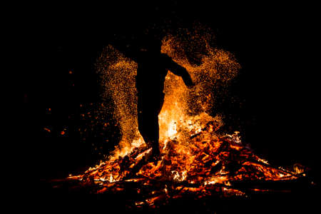 spirit: Young man is jumping above the traditional fire during celebration of Sirni Zagovezni. It is believed that evil spirits are chased away with this fire rituals.