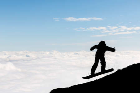 freestyle: The silhouette of a freestyle snowboarder jumping from the top of a peak of Vitosha mountain covered with clouds. He is participating in an freestyle competition of skiers and snowboarders. Stock Photo