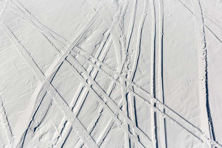 offpiste: Ski trails are seen from a aerial view of off-piste ski slope in a mountain top near a ski resort.