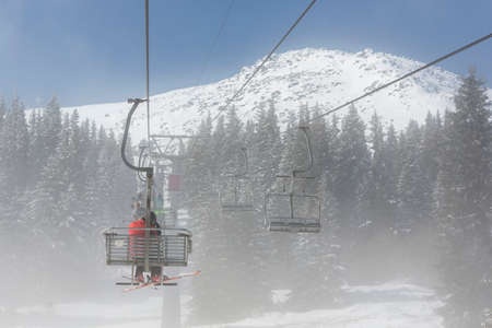 chairlift: A ski lift is transporting skiers and snowboarders into the Vitosha mountain tops ski slopes covered in fog.