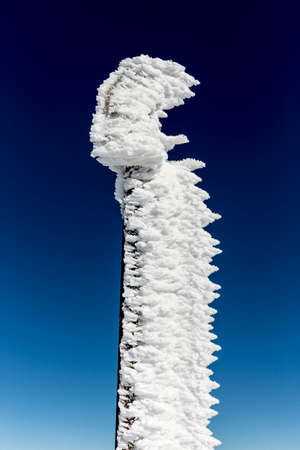high up: A frozen sign high up in the mountain top is seen against the clear blue sky in a sunny winter day. Stock Photo