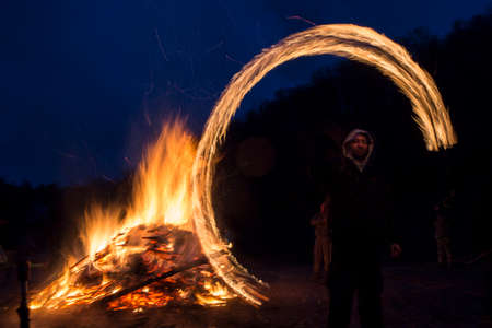 duskiness: Sofia, Bulgaria - March 13, 2016: An young man is participating in a fire ritual during a celebration of Sirni Zagovezni. It is believed that evil spirits are chased away with this fire rituals. Editorial