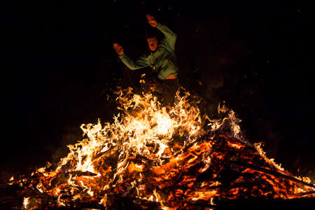 chased: Sofia, Bulgaria - March 13, 2016: An young man is participating in a fire ritual during a celebration of Sirni Zagovezni. It is believed that evil spirits are chased away with this fire rituals. Editorial