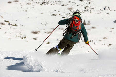 off piste: A free rider is skiing down a snowy rocky mountain top. A picture from his back. High speed.
