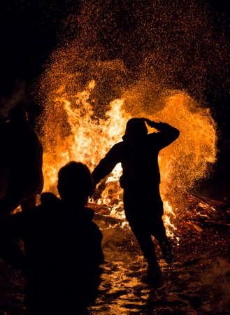 duskiness: An young man is participating in a fire ritual during a celebration of Sirni Zagovezni. It is believed that evil spirits are chased away with this fire rituals.