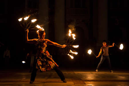perform: Sofia, Bulgaria - March 19, 2016: Performers are spinning torches while performing a fire show at night celebrating the international Earth hour event in Sofia.